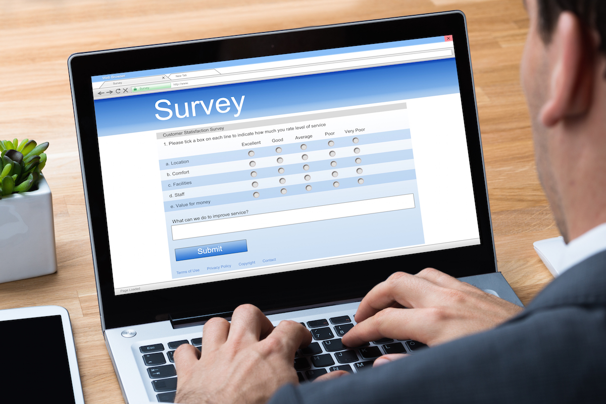 Cropped image of businessman giving online survey on laptop at office desk